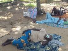 immagine di alcuni pazienti appena operati stesi per terra, all'aperto, in un campo sotto un albero con le bende agli occhi.