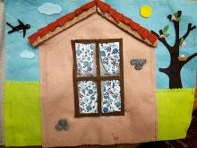 Pagina di un libro tattile che rappresenta una casa in un ambiente