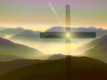 In foto una croce illuminata da una luce