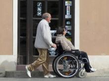 in foto persona accompagna una persona disabile