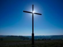 in foto una croce su cui brilla una piccola luce. Alle spalle della croce una vallata deserta e oscura
