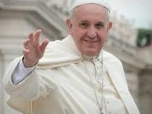 Papa Francesco fotografato mentre saluta sorridendo